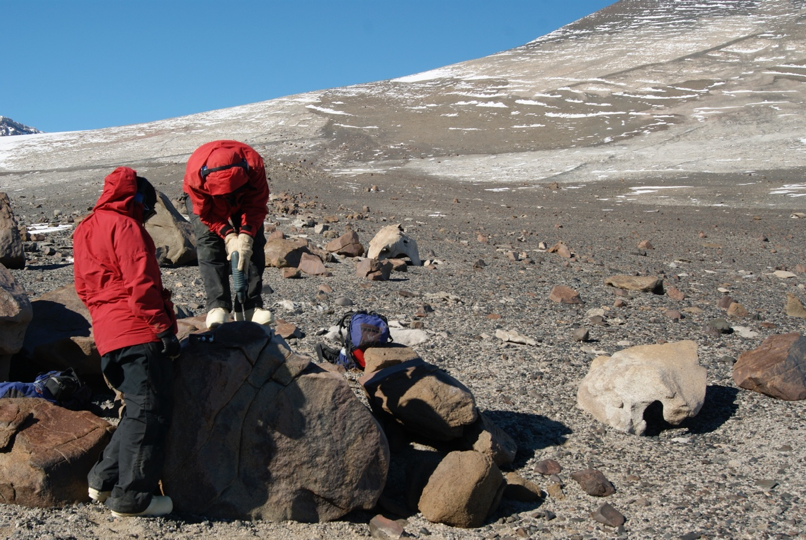 Taking a sample from a moraine boulder for cosmogenic surface exposure dating during the 2011-2012 Antarctic field season near Conrow Glacier, Wright Valley. (Photo: Jen Lamp)
