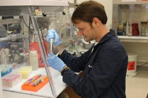 scientist pipetting under a hood
