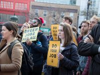 activists hold signs supporting green new deal