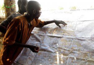 Fulani man pointing at a map