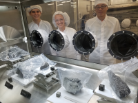 scientists in cleanroom gear looking at lunar rocks behind glass