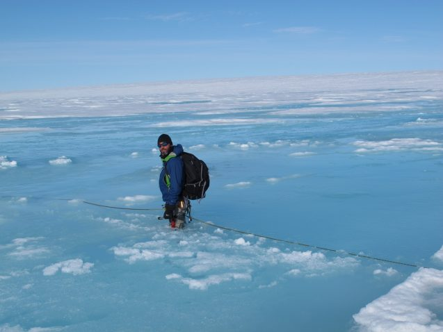 scientist stands in melting ice in Greenland