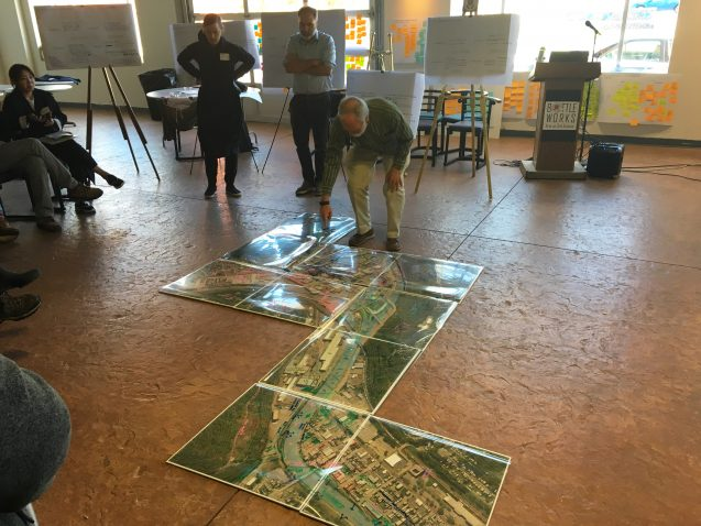 Man points at map on floor