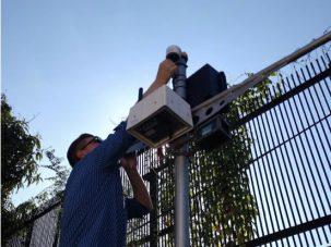 scientist installing a sensor near a fence