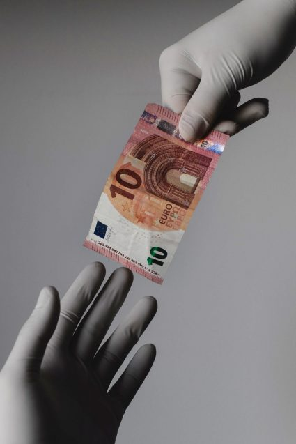 hands with latex gloves exchanging money