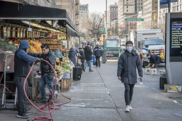 person in mask walking near fruit stand