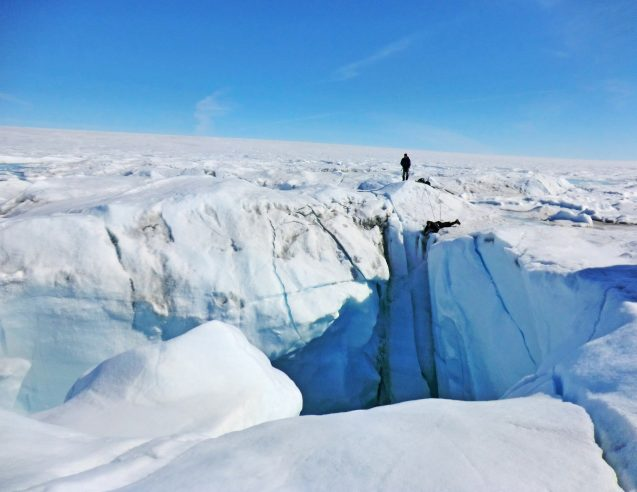 person standing near crevasse in greenland ice sheet