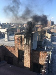 Soot and emissions pour out of a building in New York City