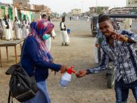 woman dispensing hand sanitizer to a man