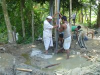 Workers install a monitoring well