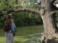 isabelle seckler stands near tree and river