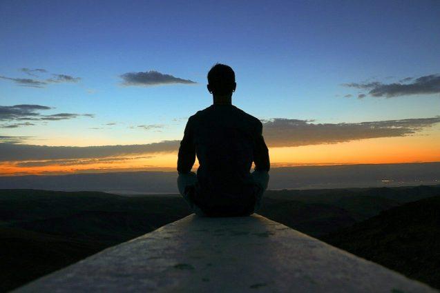 person meditating and looking at horizon
