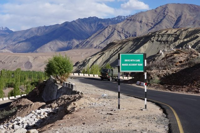 "A road disappears into the horizon of towering mountains. A sign in front of the road reads ""drive with care, makes accident rare""."