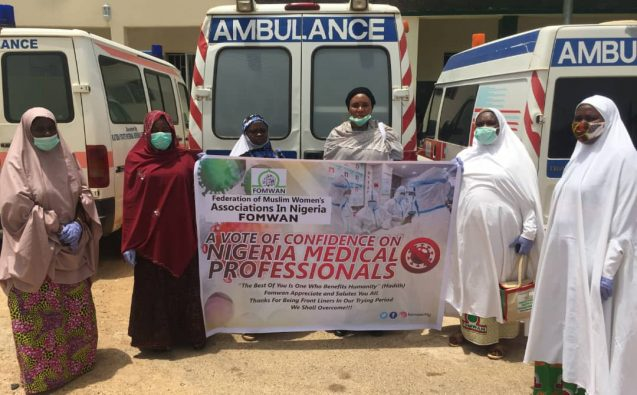 women in front of ambulance with sign