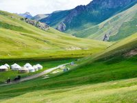 Bright green grass covers the slopes of a valley between tall hills. White yurt tents are clustered in the center of the valley.