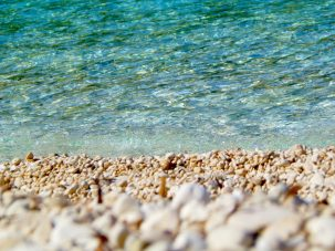 clean water and pebbles on beach