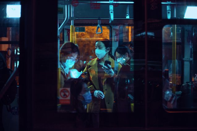 people in a bus wearing masks