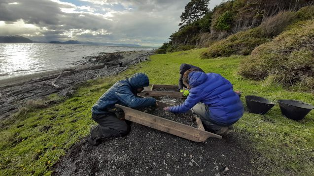Three people wear jackets sit on the ground by a body of water, sifting through dirt at an archaeological site.