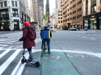 bicyclist and scooterist on nyc street corner