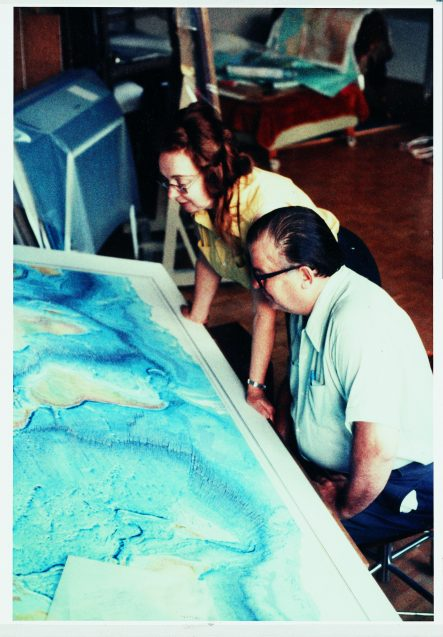 Marie Tharp and Bruce Heezen sit in front of a world map of the ocean seafloor