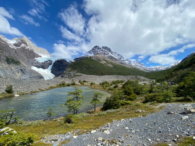 A small lake sits in the middle of a lush green meadow, with glacier-covered mountains in the background.