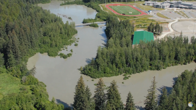 A flooded river winds through green trees. A football field can be seen in the background.