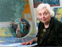marie tharp sits in front of a globe and map