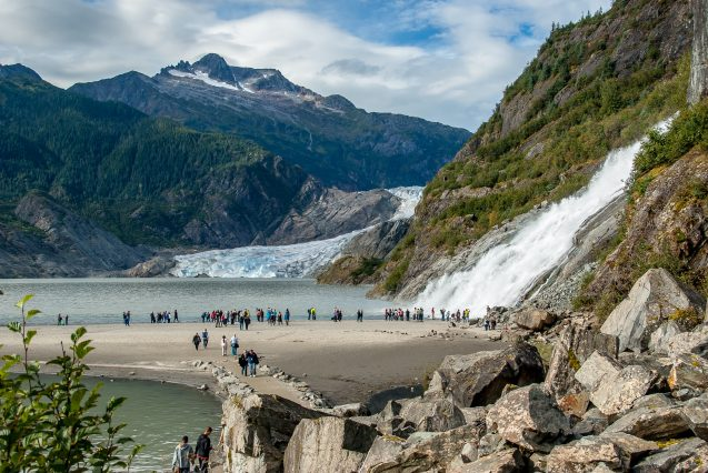 A crowd of people stand by a waterfall flowing into a lake with a glacier and mountains in the background.