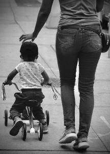 a child on a bike next to a woman