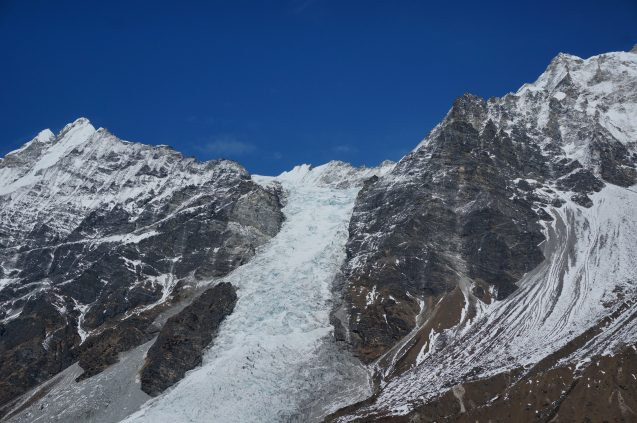 A long white glacier flows down jagged brown mountains.