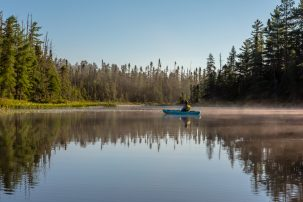 A woman kayaking along the Osgood River in Adirondack Park, New York