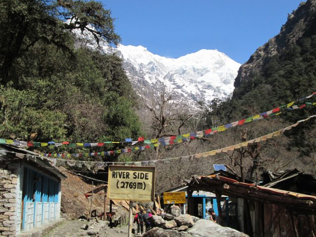 """Colorful prayer flags criss cross behind a sign that reads """"riverside"""" and above a path that leads into trees and a snow capped mountain in the distance."""