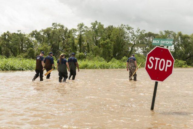 people walking through flooded street