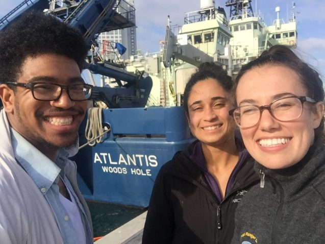 three students in front of a ship