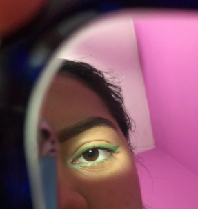 eye with green eyeshadow and pink background