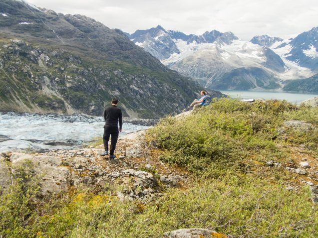 Two hikers on a rocky and grassy mound in front of a glacier and mountains in the background.