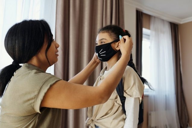 a mother puts a mask on her daughter