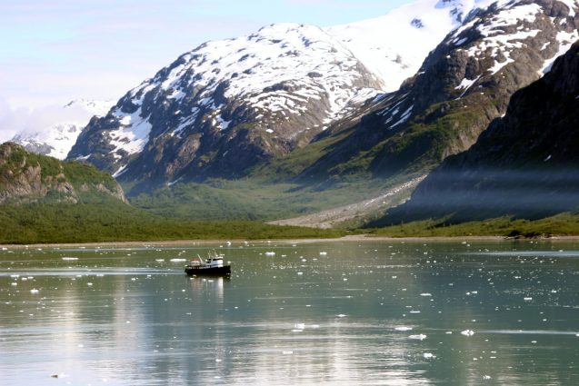 A boat moves across a clear lake with snowy mountains in the background.