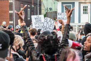 A protester raising her middle fingers during a Black Lives Matters rally in Buffalo New York
