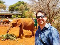 man in sunglasses near baby elephant
