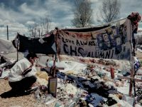 A man kneels before a cross at a make-shift memorial outside Columbine High School near Denver, CO after a mass shooting there in April of 1999