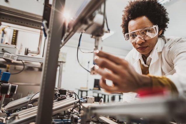 Low angle view of African American lab worker examining machine part while working in a lab.