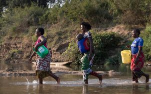 women crossing river carrying babies and water