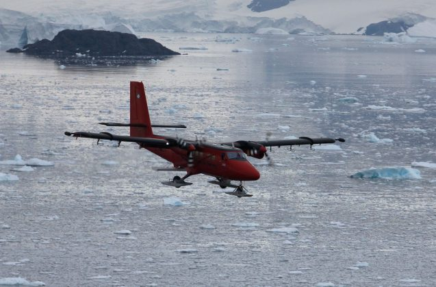 small plane flying over icy water