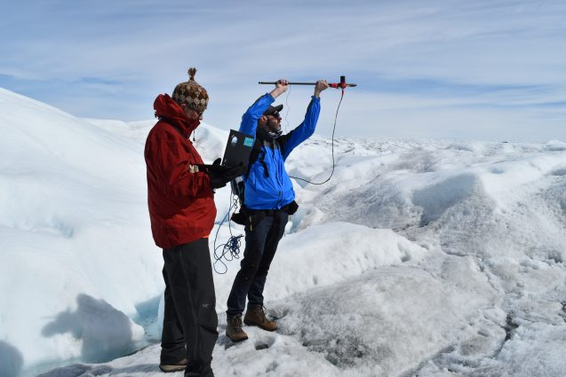 researchers measuring reflectivity of greenland ice sheet