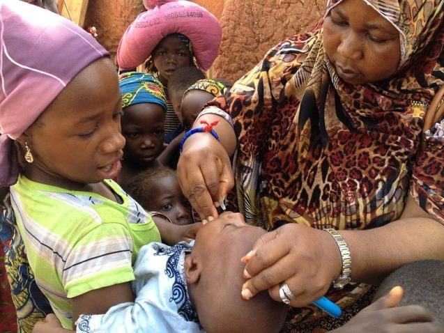 Woman administering polio vaccine to a child