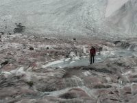 Researchers standing on a dirty glacier