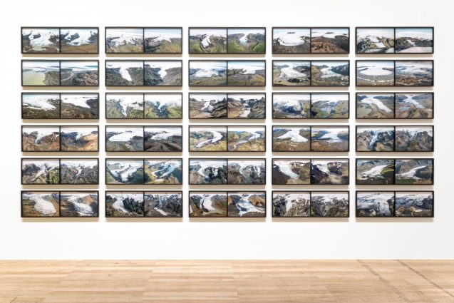 a block of 30 images on a white wall, each image shows the same glacier over the span of twenty years