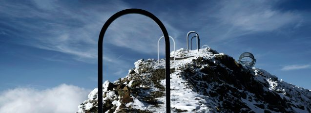 a black archway frames a snowy glacier pathway with other archways in black and white