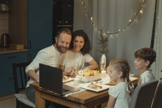 family gathered at table for dinner and looking at computer